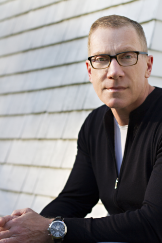James Swan in a black zip up sweater sitting on a rooftop