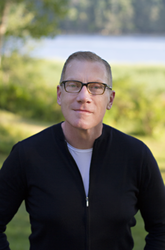 James Swan in a black zip up sweater posing in an idyllic setting with a body of water in the background